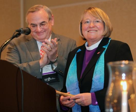 Bishop Larry Goodpaster passes the gavel of leadership to his successor, Bishop Rosemarie Wenner. Photo credit: United Methodist News Service / Kathleen Barry.