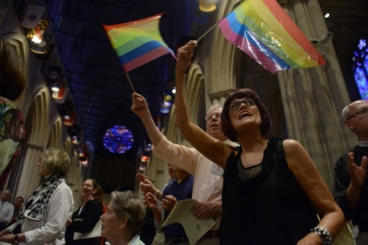 Beth Pattison, front right, and husband John Pattison, wave rainbow flags during a prayer service for the Lesbian Gay Bisexual Transgender community to mark the Supreme Court's ruling at the National Cathedral on June 26 in Washington. (Photo Credit: Jahi Chikwendiu/Washington Post)